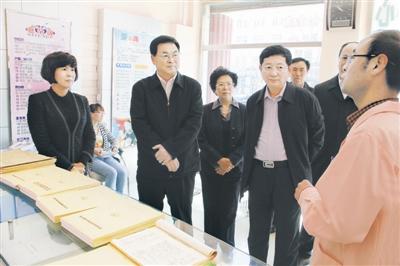 亚平(左二)在科尔沁区人口计生服务站调研,认真听取干部群众意