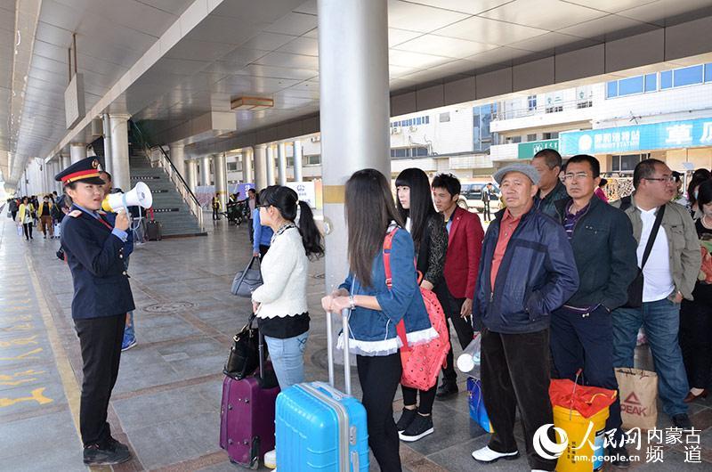 车站工作人员组织旅客有序排队等候列车