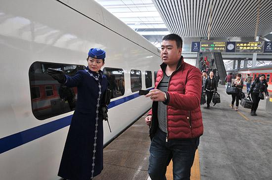 图为动车组列车乘务员正在引导旅客上车
