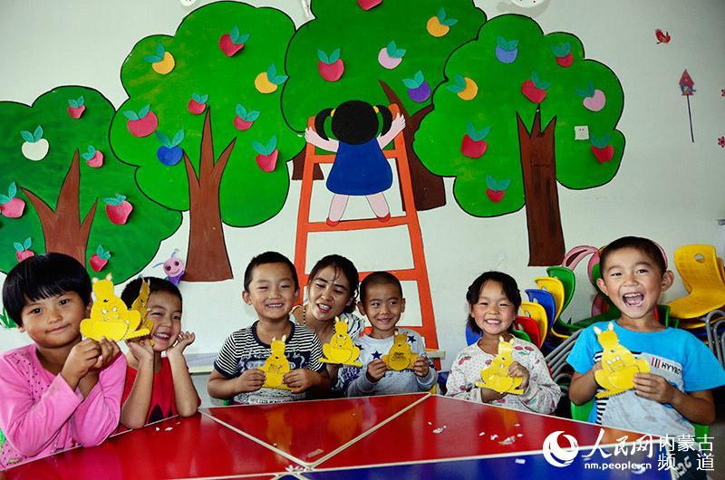通辽市开鲁县三星村幼儿园的小朋友在新建的校舍展示自己刚做好的手工