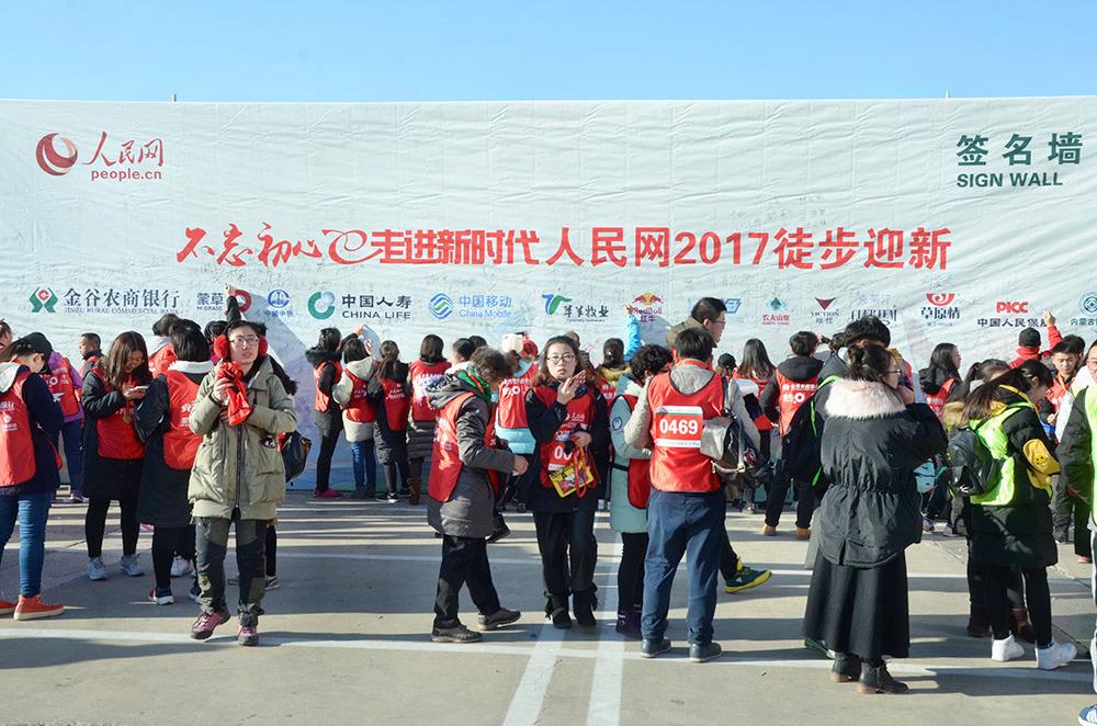 参加活动的市民和徒步爱好者们在活动签名墙上签名
