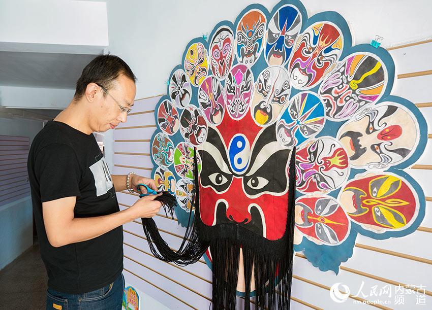 呼和浩特市玉泉区恒昌店巷小学老师在修饰手工制作的京剧脸谱.