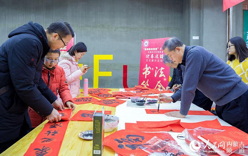 玉泉区民间文艺家协会会员现场为市民书写春联。