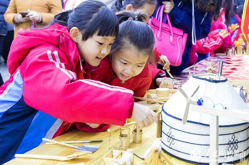 小朋友在欣赏蒙古包摆件。