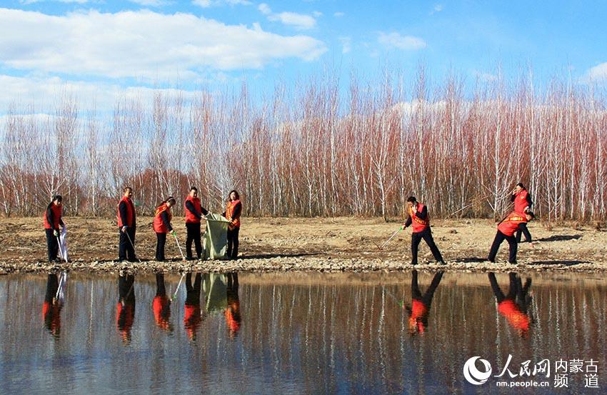 4月9日,黨員、志願者等在內蒙古自治區扎蘭屯市雅魯河畔撿拾垃圾,保護母親河。