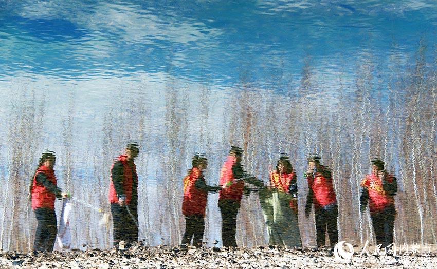 4月9日,黨員、志願者等在內蒙古自治區扎蘭屯市雅魯河畔撿拾垃圾,保護母親河。(圖片為垂直翻轉180°拍攝)