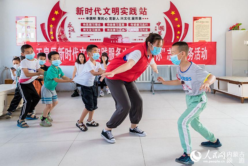 """呼和浩特市玉泉区新时代文明实践服务中心志愿者带领孩子们做""""鹰捉小鸡""""游戏。丁根厚摄"""