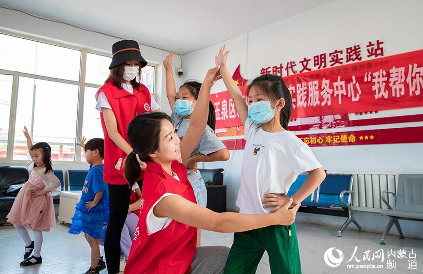呼和浩特市玉泉区新时代文明实践服务中心志愿者教孩子舞蹈动作要领。丁根厚摄