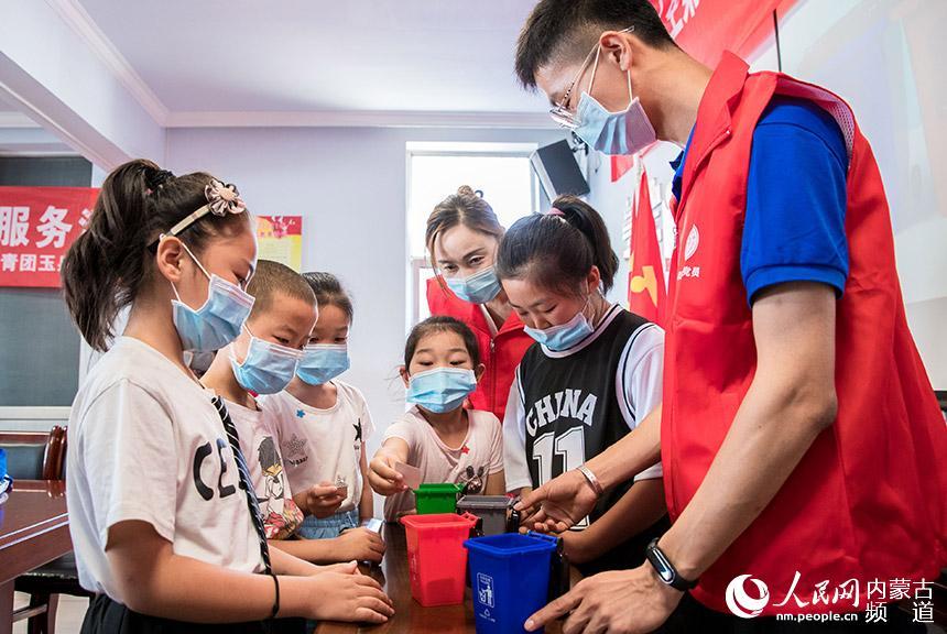 呼和浩特市玉泉区新时代文明实践服务中心志愿者与孩子做垃圾分类知识互动游戏。丁根厚摄
